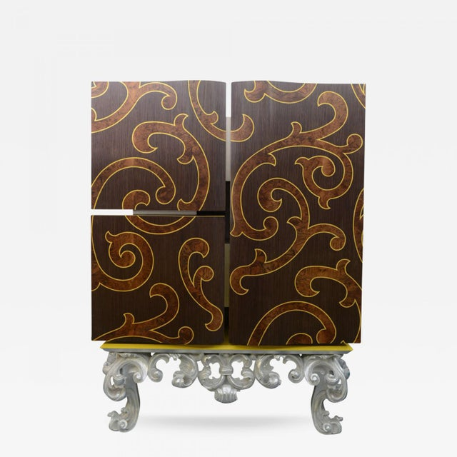 """The doors all inlaid in """"C"""" scrolls with mixed woods opening to reveal a geometric painted finish and compartments, all on..."""