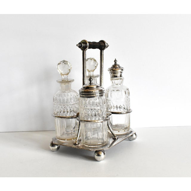 An antique Victorian silverplate and cut glass condiment caddy set. The caddy features ball feet and a turned wood handle....