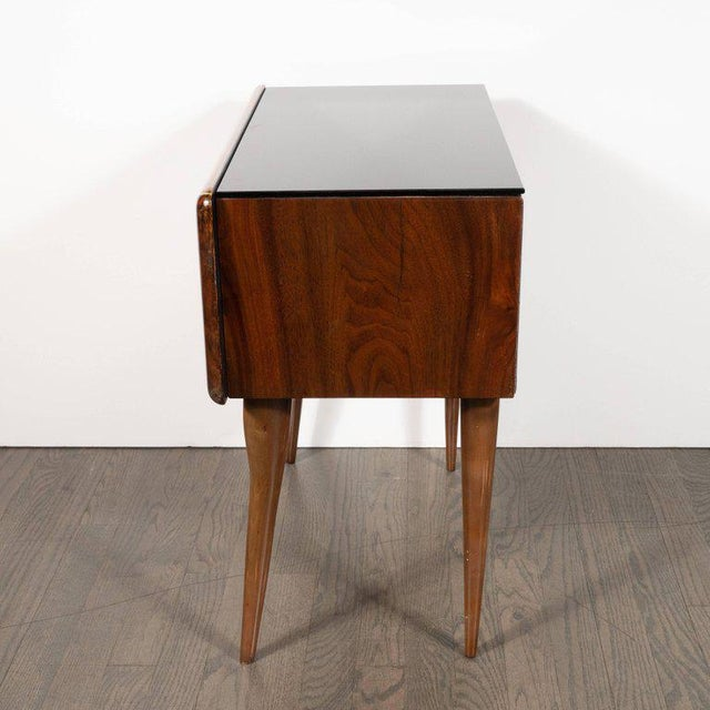 This sophisticated pair of nightstand/ end tables were realized in Italy, circa 1950. They feature black vitrolite tops; a...