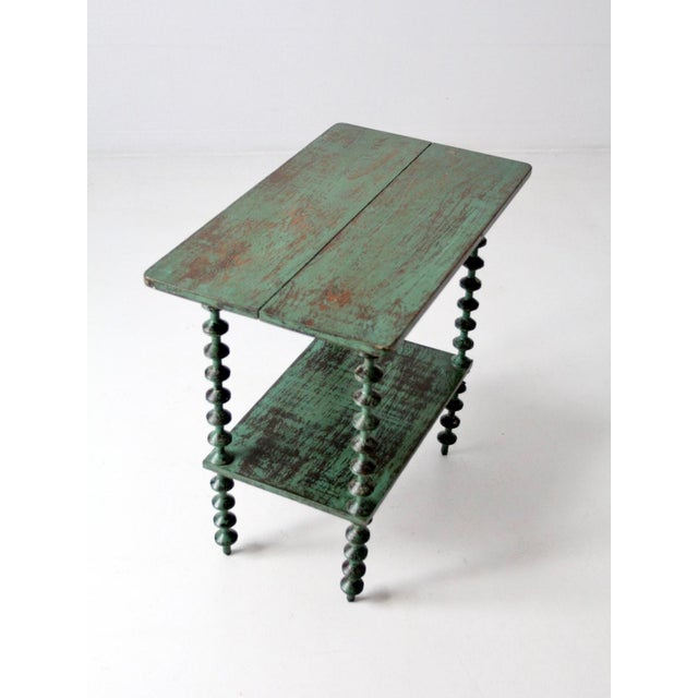 This is an antique folk art spool table circa 1900. Wooden spools shape the table legs with a wooden table top and shelf....