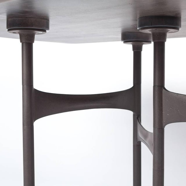 The whole-log book-matched slab Link dining table is a modular system comprising patinated cast aluminum and steel...