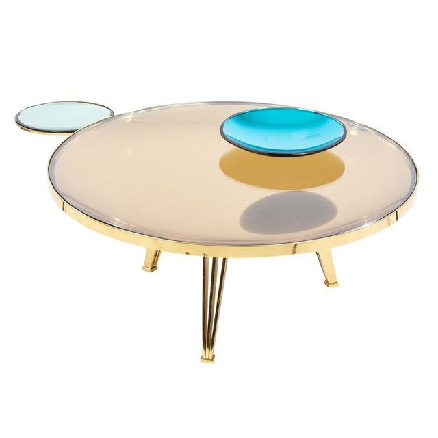 The Riflesso coffee table designed by Gaspare Asaro features a main tinted and mirrored concave glass topped with a clear...