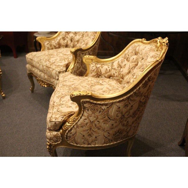 Brilliantly gold upholstered Italian 1950s Hollywood Regency slipper chairs with fantastic floral and scrolling on the...