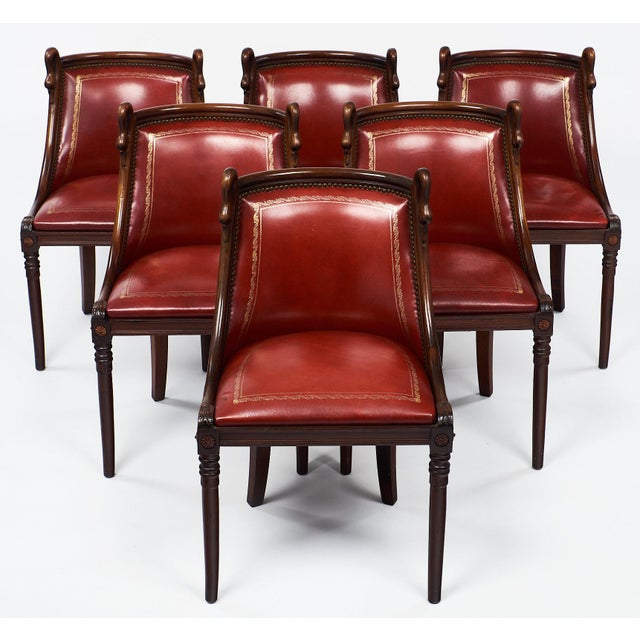 A charming set of Empire style chairs made of mahogany with hand carved swan neck details adorning the barrel backs. The...