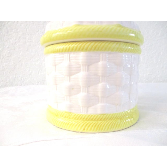 Vintage white and yellow basket weave design lidded canister with applied figural leafed lemons on center of lid. Circa...