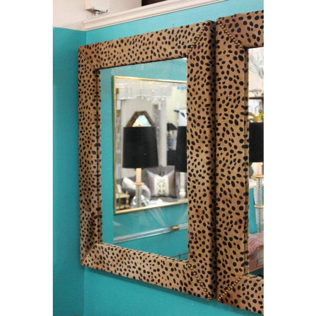 Pair of mid century modern mirrors framed with faux leopard real leather with brass nailheads. The pair is in great...