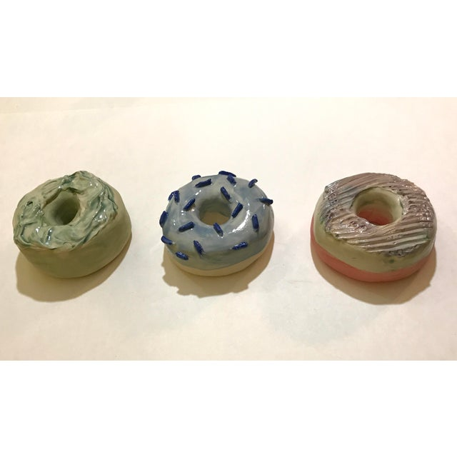 Handmade stoneware clay donuts. Each donut I form out of a slab (flat sheet of clay) and build it hollow. I then hand...