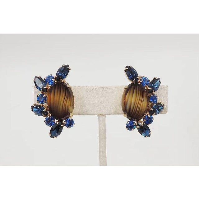 """Goldtone striped brown rhinestone with marquise faux-sapphire clip back earrings. Marked """"Carnegie."""" Measure: 1 3/8 inches..."""