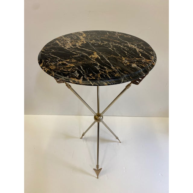 Stunning campaign style side table in the manner of Maison Jansen having brass and steel arrow motif base and handsome...