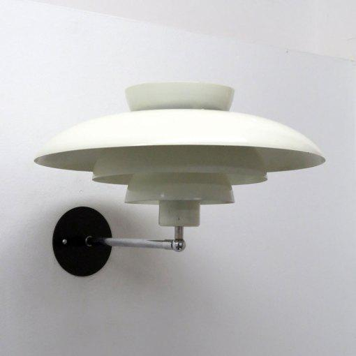 Wonderful tiered danish wall light by Horn with white enameled metal rings of different sizes perched on a minimal chrome...