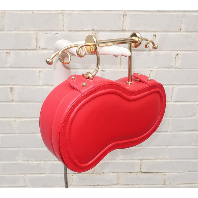 This red leather Italian handbag definitely puts the fun into fashion with both a unique silhouette and a sensationally...