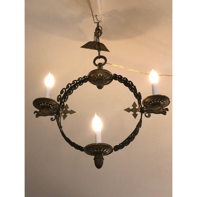 A pair of rare iron and antiqued brass light fixtures having an open circle with iron curlicue scrollwork, around which...