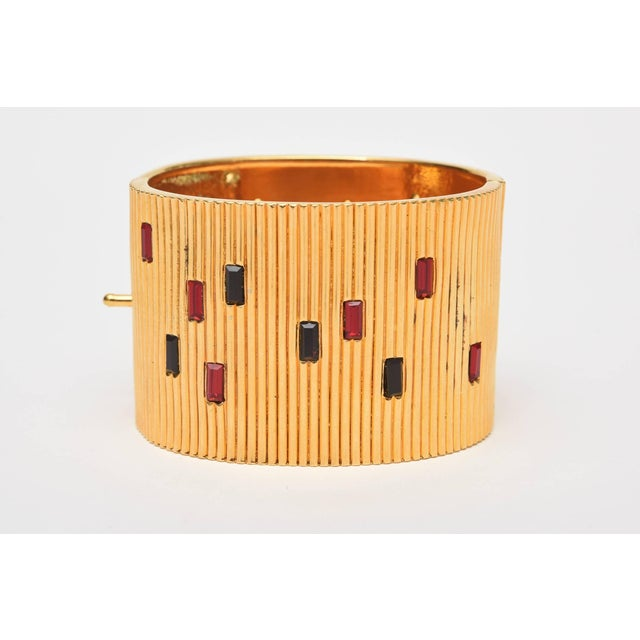 This wide-ribbed cuff gold toned Bracelet, with red and black glass inserts is by Paloma Picasso. On the tag on the...