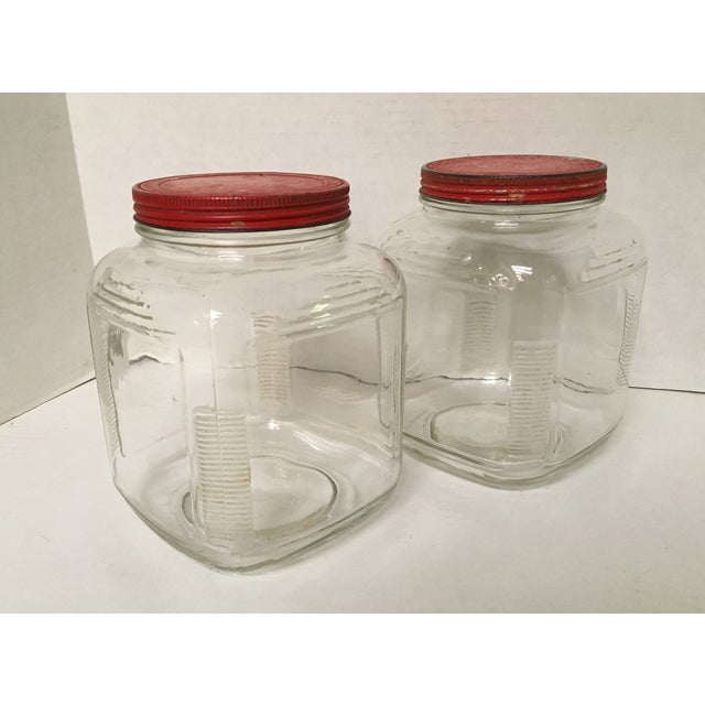 Square ribbed edge vintage glass Hoosier canisters with original red metal lids. This large pair of mid-century jars work...