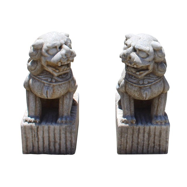 This is a pair of handcrafted Off white brownish marble stone Foo Dogs with traditional Chinese details. There is scroll...