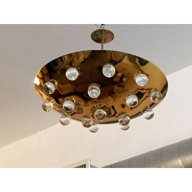 A wonderful pair of 1960s French gold-plated brass round disc fixture with 16 solid glass orbs. Five-light sources which...