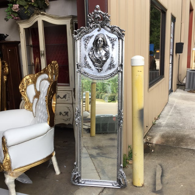 Gorgeous silver floor mirror topped by a bust of a beauty.
