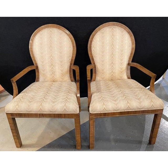 Pair of Mid-Century Modern arm chairs by Milo Baughman. Each with burlwood frames having brass framing. Made by Mastercraft.