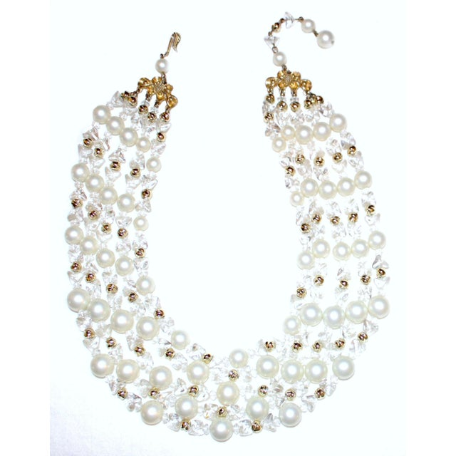 Circa 1960s Schiaparelli multi-strand bib necklace with white faux-pearls embellished with clear glass and gold tone metal...