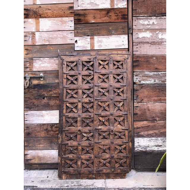 This 19th century wood carved door features original hand-forged metal square studs, straps, and hardware. The face of the...