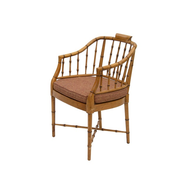 Faux bamboo chinoiserie style armchair in natural wood with caned seat. Seat cushion is in a burnt orange chenille and is...
