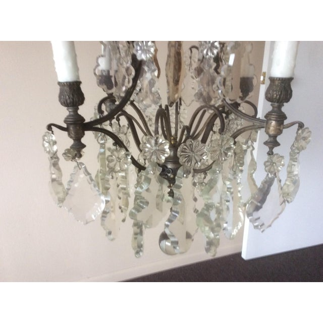 Great slightly narrower than usual for its height four light chandelier. Some of the antique cut Crystal prisms have a...
