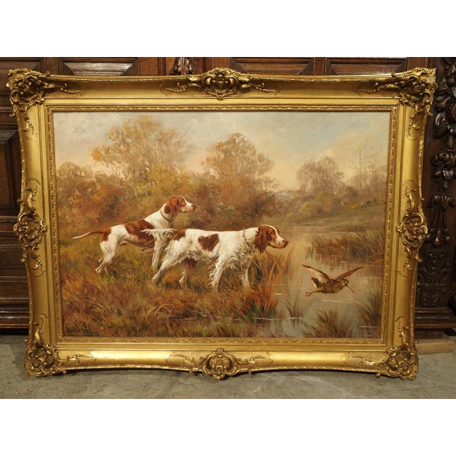 This antique French gilt framed hunting painting depicts two bird dogs, one flat coated and one with long hair in the...