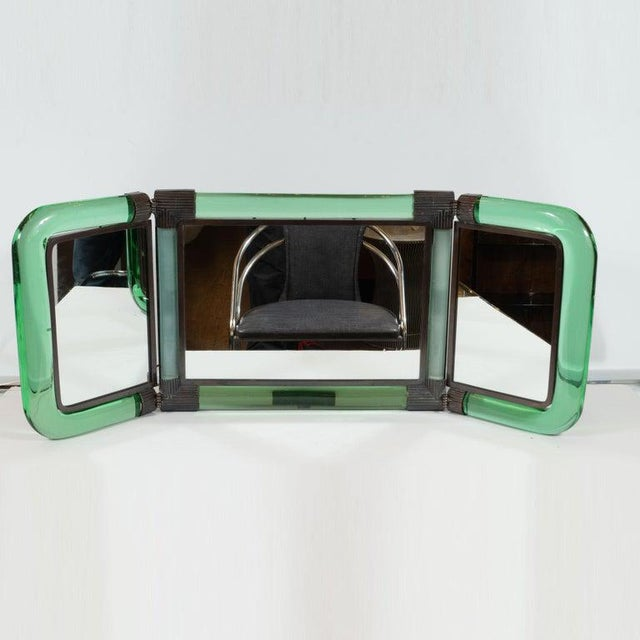 This stunning and dramatic three-piece Mid-Century Modern illuminated table/vanity mirror was realized in Italy, circa...