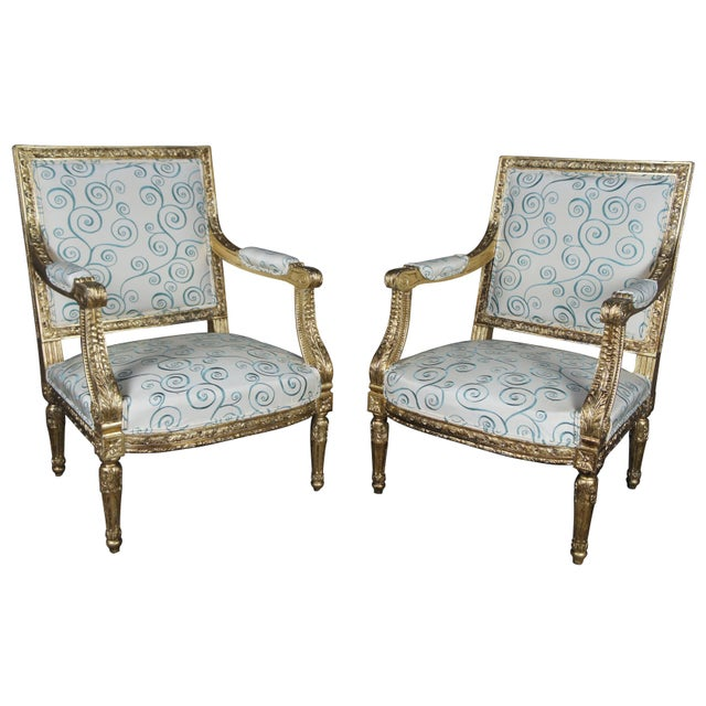 Late 19th century Louis XVI fauteuils. An ornate pair with modern upholstery, trimmed in gold with acanthus detail and...