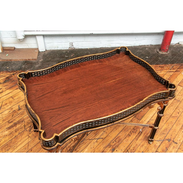 A beautifully crafted carved, ebonized and gilt serpentine tray table. The detachable tray is pierced with a banded...