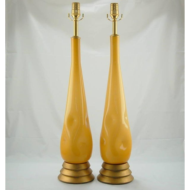 Vintage pair of Murano glass table lamps. An inner layer of white Venetian glass surrounded by layers of BUTTERSCOTCH...