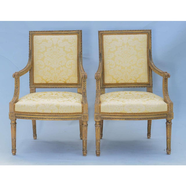 Pair of open armchairs, distressed painted and parcel gilt finish, each having square upholstered back wonderfully carved...
