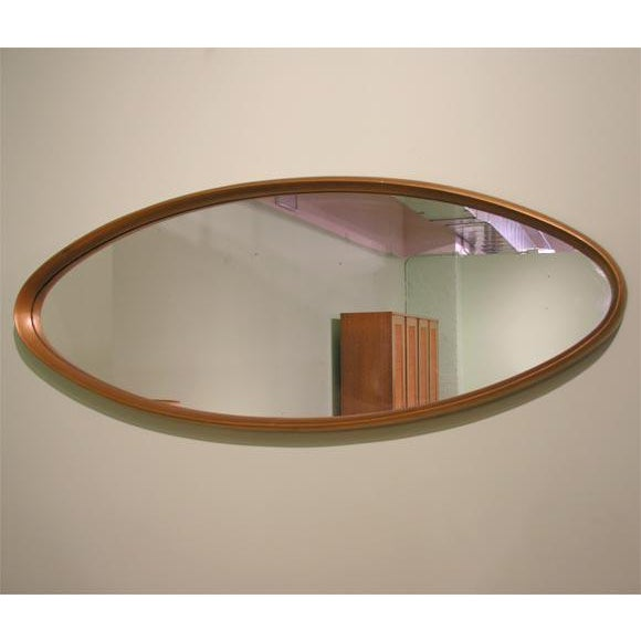 Sinuous, elegant gilt wood framed oval mirror. American, circa 1950.