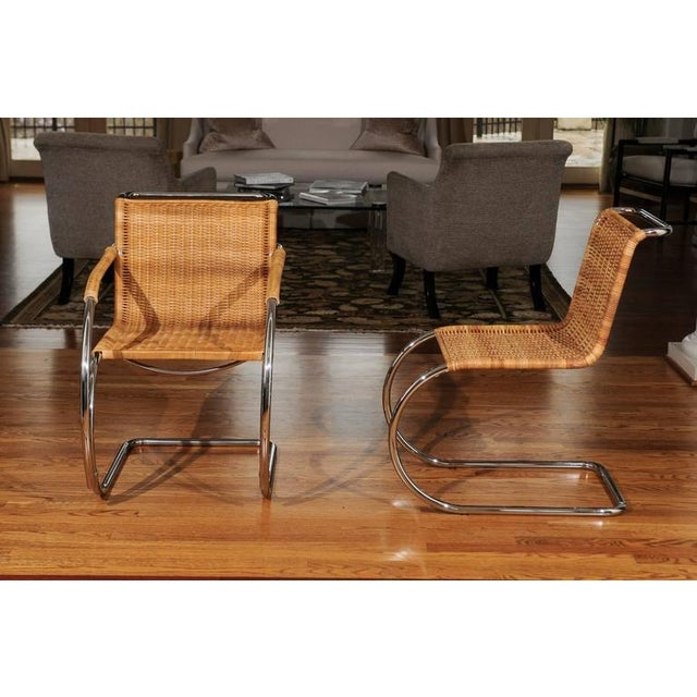A fabulous set of eight (8) vintage wicker and chrome dining chairs, circa 1970. Stellar quality and craftsmanship. This...