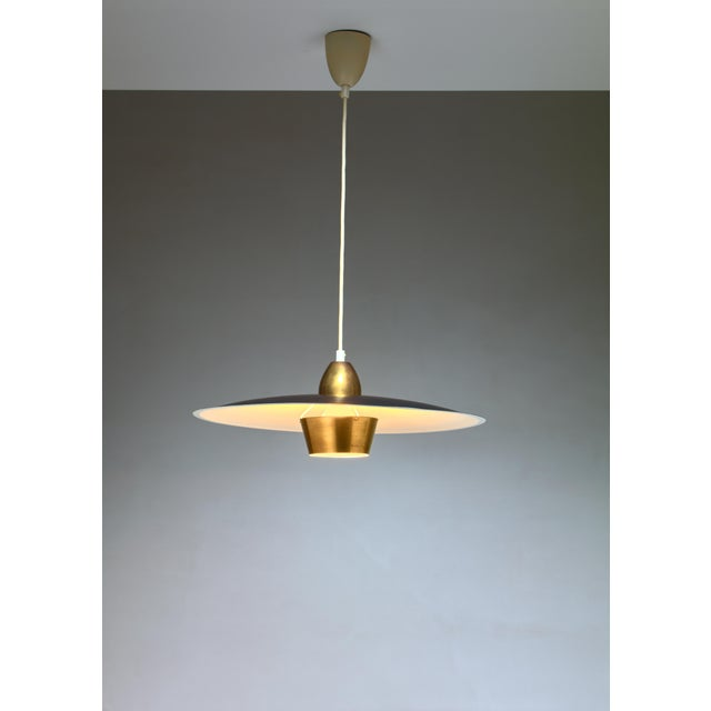 One of a pair of model T-21 pendant lamps by Swedish silversmith and designer Sigvard Bernadotte (1907 - 2002), made of a...