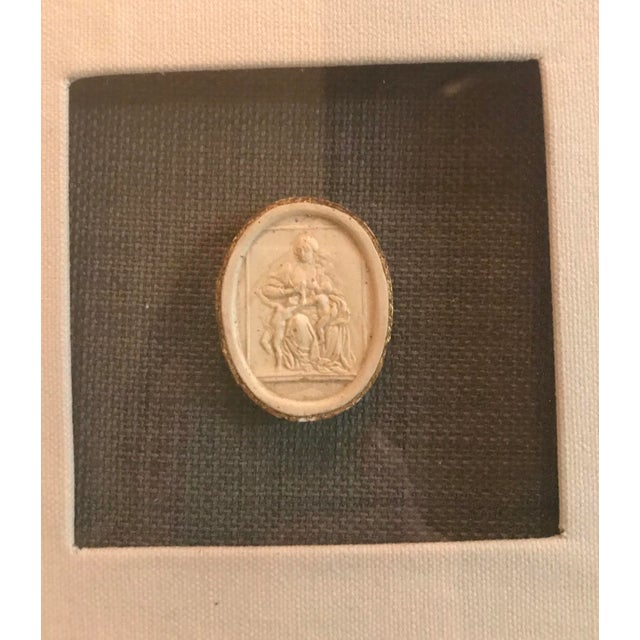 "2"" plaster intaglio has gold leafed edges mounted on dark gray fabric, centered in a white fabric covered mat. Wood frame..."