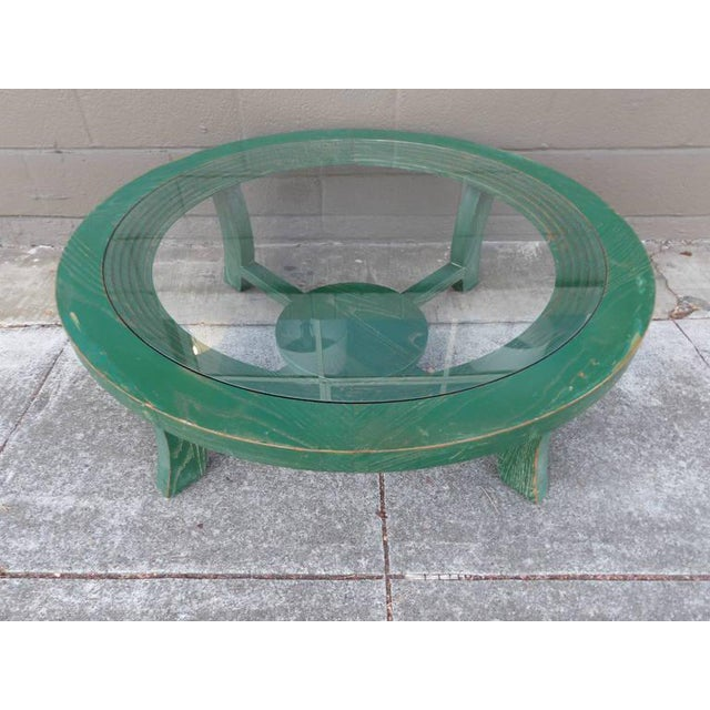 A Paul Frankl cerused oak circular coffee table with a glass top. Circa. 1948. Crafted in solid oak with an unusual,...