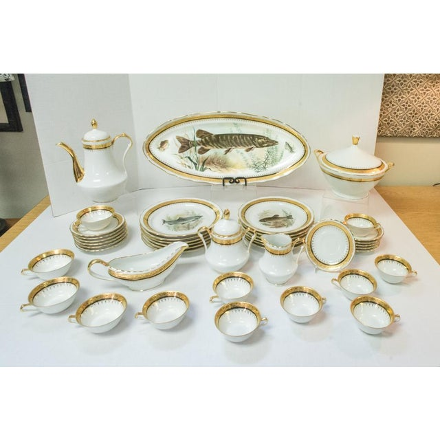French Porcelain Dinner set of 42 pieces, hand-decorated with 24K gold paint accented with a thin black banding. Set...