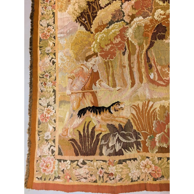 A European Old World pictorial tapestry depicting a spear carrying young hunter in 18th century costume accompanied by his...