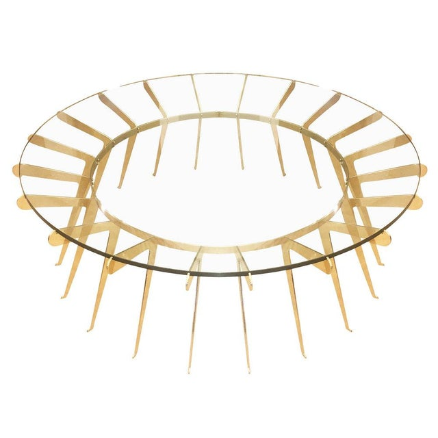 Contemporary coffee table designed by Gaspare Asaro for formA featuring twenty brass legs supporting a thick glass top....