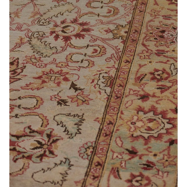 This revival Agra rug has a shaded ivory-grey field with an overall design of shaded burgundy-red, apricot and light green...