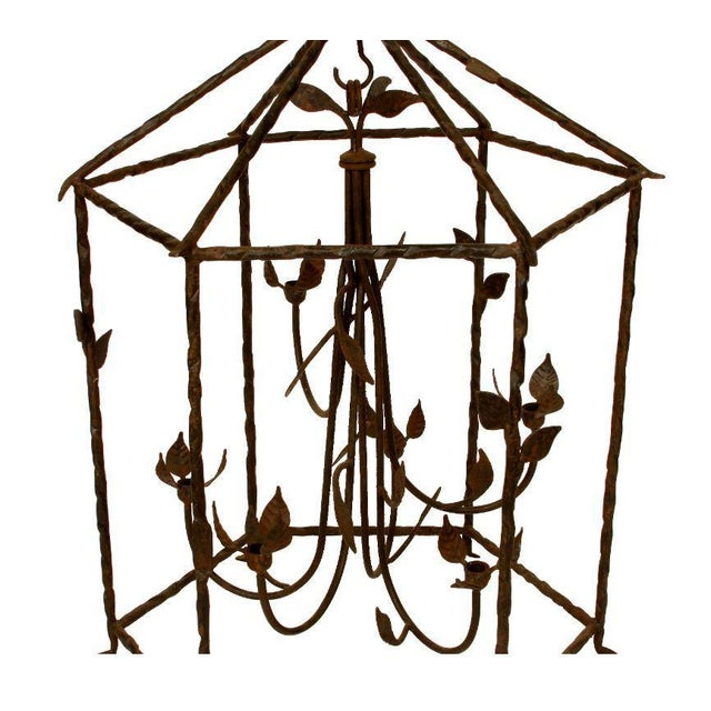 Large iron foliate lantern unelectrified. Six curved candle arms with an iron cage lantern surround.