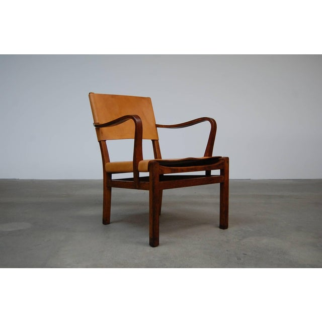 Lounge chair in oak and leather, with beautifully sculpted arms, designed by Axel Einar Hjorth, circa 1940. Produced by...