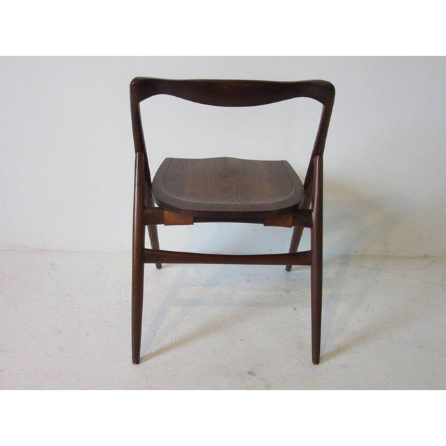 A studio crafted oiled black walnut sculptural chair in the manner of George Nakashima designed and made by Japanese...