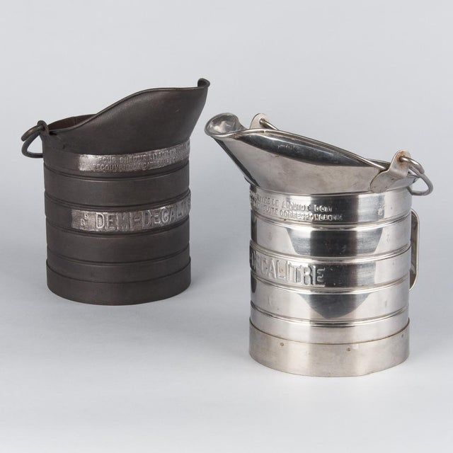 Vintage metal milk measuring pitcher from France, circa 1950. The polished steel pot has a tall, wide pouring spout and...