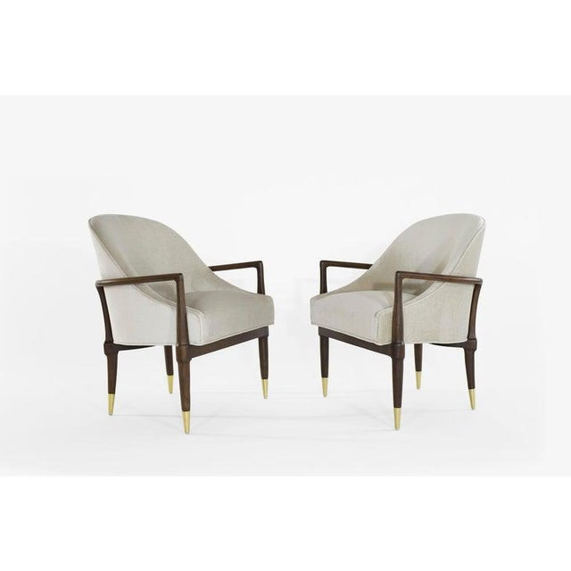 Pair of lounge chairs in the style of Gio Ponti, featuring completely restored sculptural walnut framing and brass sabots....