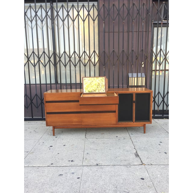 Mid Century Lowboy Dresser With Hidden Vanity and black detailing through out. Designed by H. Paul Browning for...
