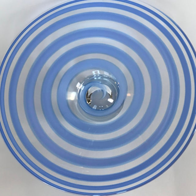 This stunning hand-blown art glass centerpiece bowl features a periwinkle blue ribbon spiral design in clear glass. The...