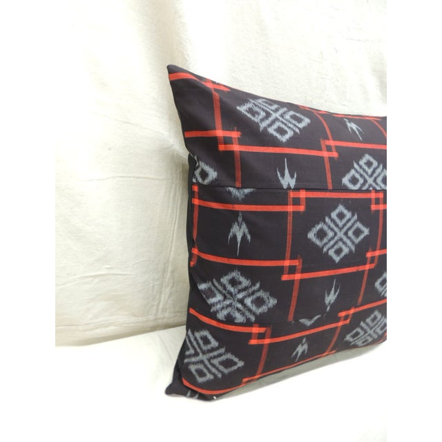 Pair of Asian red and black Ikat woven textile square decorative pillows. Black solid cotton backing. Zipper closure and...
