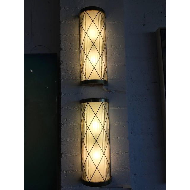 A pair of wall-mounted brass and glass sconces. Nice Hollywood Regency styling. We believe these sconces are American but...
